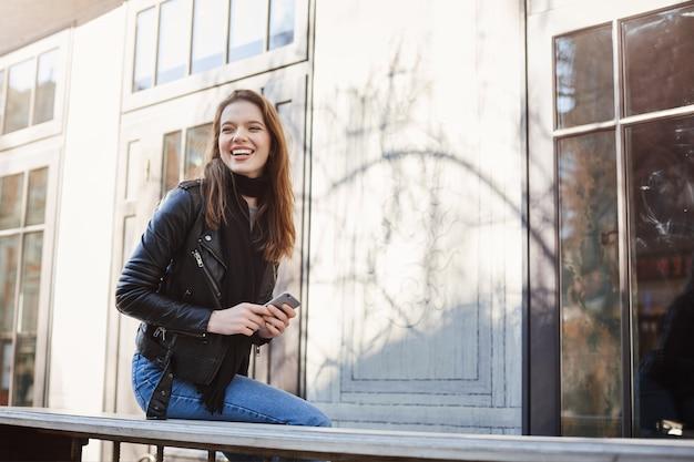 Aantrekkelijke vrouw die in stad loopt, dichtbij koffie zit, lachend over grappige kerel die probeert indruk op haar te maken, houdend smartphone.