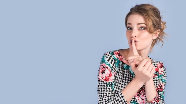 Aantrekkelijke vrouw die kalm gebaar in elegante kleding toont