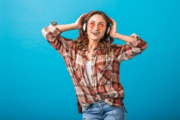 Aantrekkelijke vrouw die lacht genieten van het luisteren naar muziek in hoofdtelefoons in geruit overhemd en spijkerbroek geïsoleerd op blauwe studio achtergrond, roze zonnebril dragen