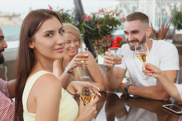 Aantrekkelijke vrouw die lacht naar de camera tijdens het drinken met haar vrienden in de bar op het dak