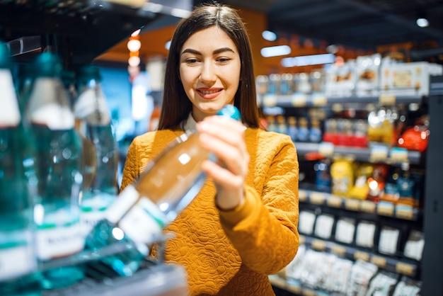 Aantrekkelijke vrouw die mineraalwater kiest in de supermarkt