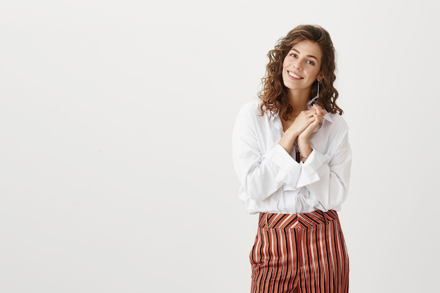 Aantrekkelijke vrouw die ontroerd kijkt, blij om een compliment te ontvangen