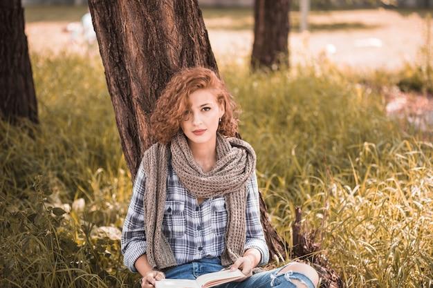 Aantrekkelijke vrouw die op boom leunt en boek in openbare tuin houdt
