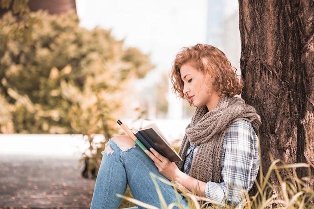 Aantrekkelijke vrouw die op boom leunt en boek in zonnig park leest
