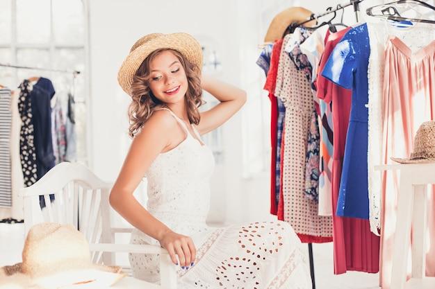 Aantrekkelijke vrouw die op een hoed probeert. gelukkig winkelen in de zomer.