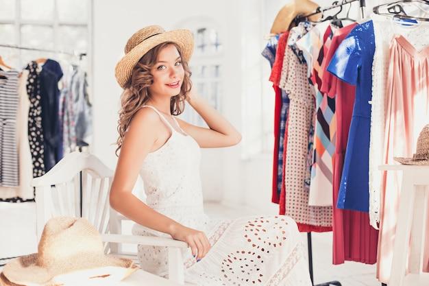 Aantrekkelijke vrouw die op een hoed probeert. gelukkig zomer winkelen.