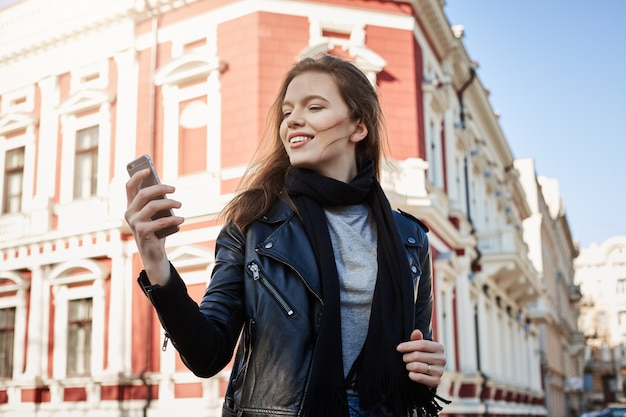 Aantrekkelijke vrouw die rond stad loopt, die smartphone houdt