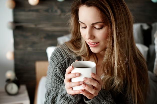 Aantrekkelijke vrouw die 's ochtends koffie drinkt