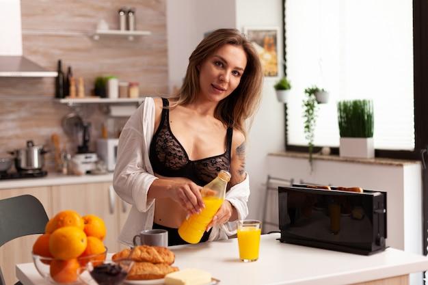 Aantrekkelijke vrouw die sap giet tijdens het ontbijt in sexy lingerie