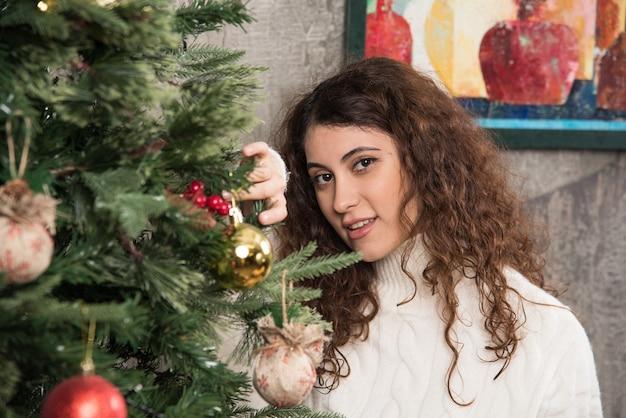 Aantrekkelijke vrouw die staat en naar de camera kijkt in de buurt van de kerstboom