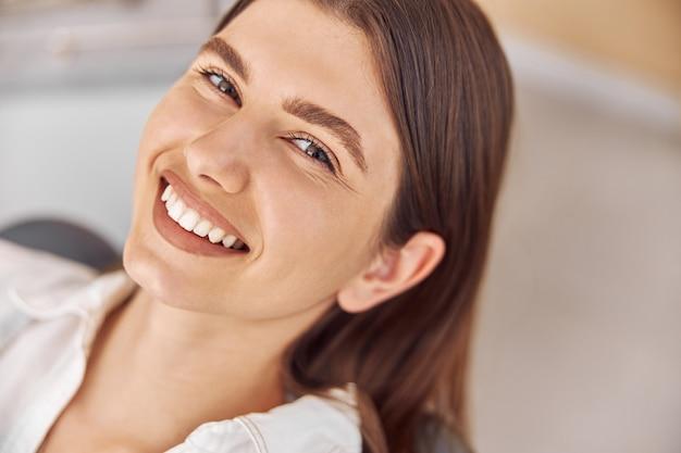 Aantrekkelijke vrouw die tandheelkundige kliniek bezoekt. gelukkige jonge vrouw die als tandartsstoel zit op het tandartskantoor.