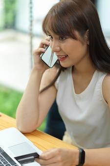 Aantrekkelijke vrouw die telefoneert en een mobiele telefoon met creditcard vasthoudt met een leeg leeg scherm