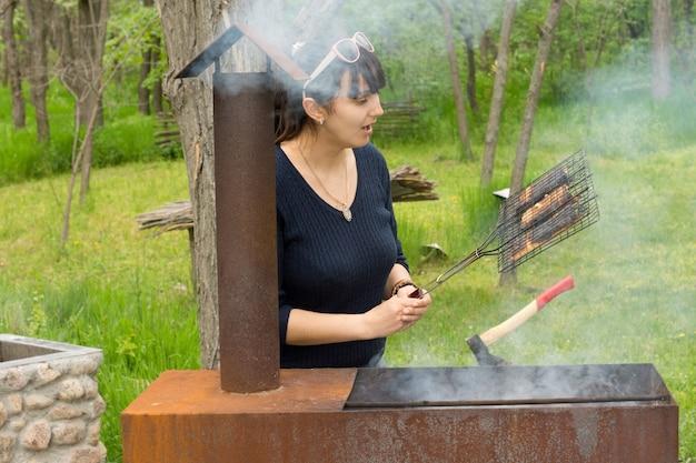 Aantrekkelijke vrouw die vlees kookt boven een barbecue