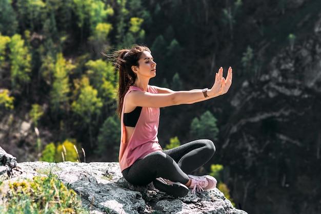 Aantrekkelijke vrouw die yoga doet. gezonde levensstijl. de concentratie van het lichaam. vrouw doet yoga in de bergen. meisje doet yoga bij zonsondergang. vrouw mediteert in de natuur. meditatie in de bergen