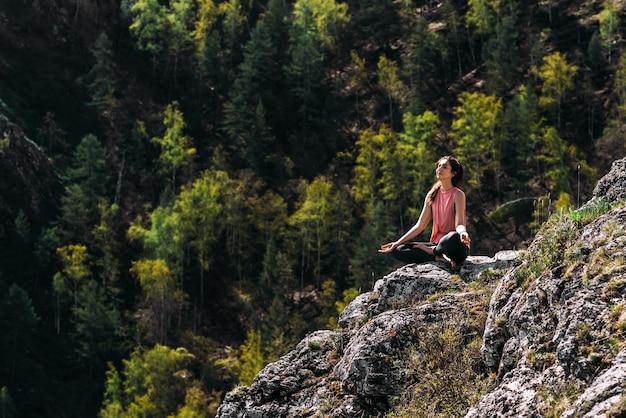 Aantrekkelijke vrouw die yoga doet. gezonde levensstijl. vrouw doet yoga in de bergen. meisje doet yoga bij zonsopgang. vrouw mediteert in de natuur. meditatie in de bergen. ruimte kopiëren