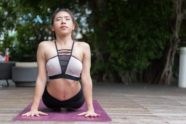 Aantrekkelijke vrouw die yoga speelt voor haar goede gezondheid