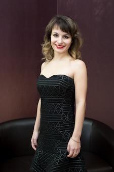 Aantrekkelijke vrouw die zich voordeed op zwarte jurk