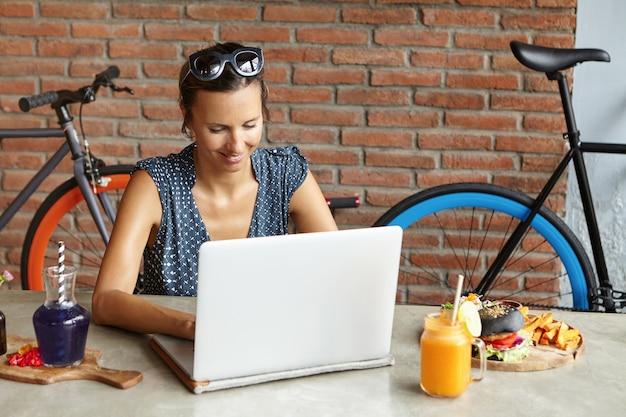 Aantrekkelijke vrouw die zonnebril op haar hoofd draagt dat online winkelt, gebruikend snelle internetverbinding, zittend voor open laptop computer tijdens lunch