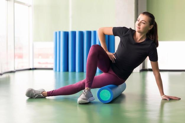 Aantrekkelijke vrouw doet schuim roller oefening en poseren in moderne lichte fitness center