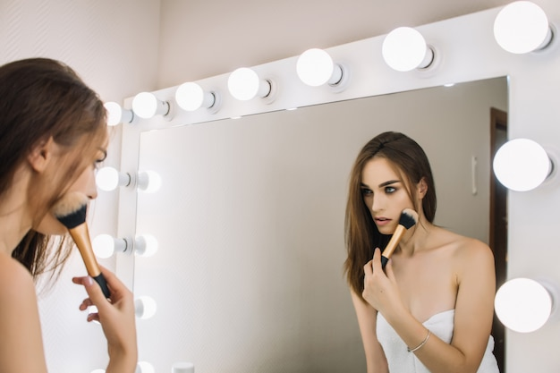 Aantrekkelijke vrouw doet stijlvolle avond make-over, rokerige ogen, perfecte huidskleur