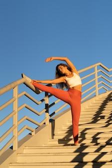 Aantrekkelijke vrouw doet stretchoefening buiten op trappen