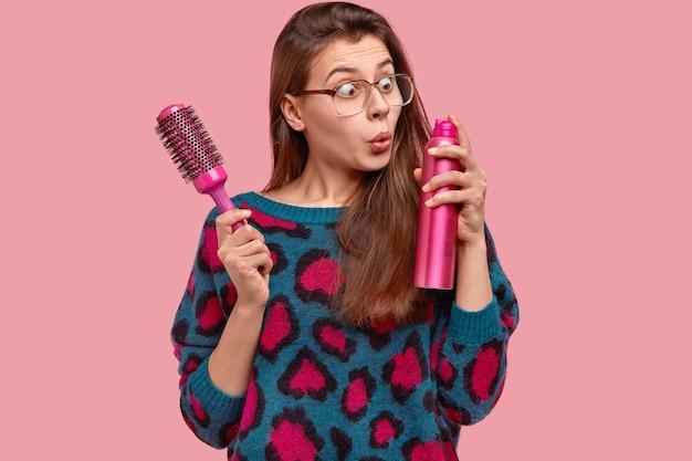 Aantrekkelijke vrouw draagt een grote vierkante bril, staart stomverbaasd naar haarlak, houdt haarborstel vast, wil een kapsel maken voor een speciale gelegenheid