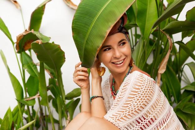 Aantrekkelijke vrouw draagt een kleurrijke hoofddoek als een tulband en grote ronde oorbellen