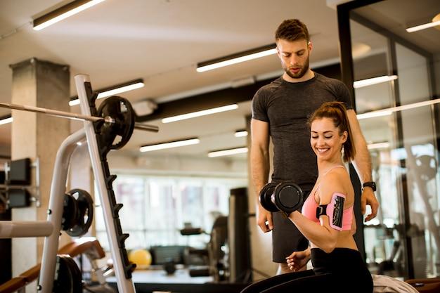 Aantrekkelijke vrouw en een persoonlijke trainer met gewichtheffen bij gymnastiek