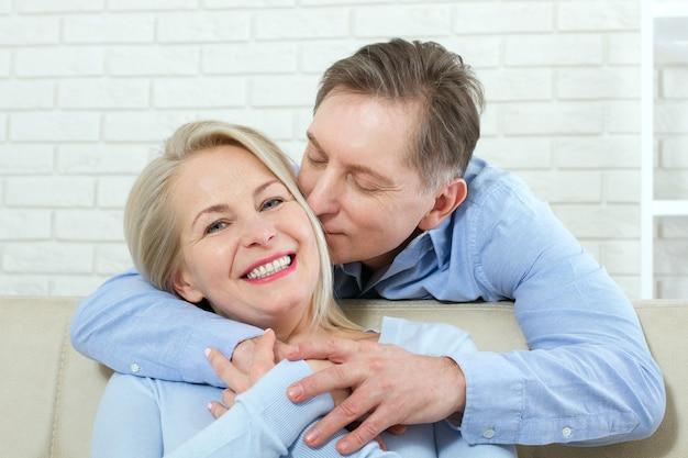 Aantrekkelijke vrouw en man, hij knuffelt haar van achteren en kust op de bank