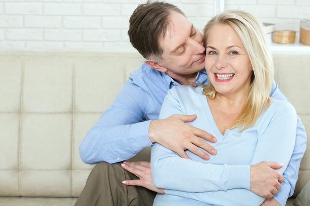 Aantrekkelijke vrouw en man in een omhelzing in de woonkamer.