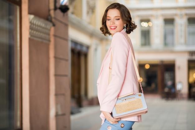 Aantrekkelijke vrouw gekleed in trendy outfit wandelen in de straat bij het winkelen