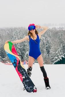 Aantrekkelijke vrouw gekleed in zwembroek met snowboard op de helling