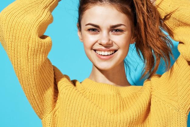 Aantrekkelijke vrouw gele trui studio geïsoleerde achtergrond