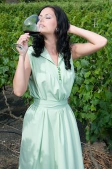 Aantrekkelijke vrouw geniet van een dag tussen de wijngaarden en geniet van een goede wijn