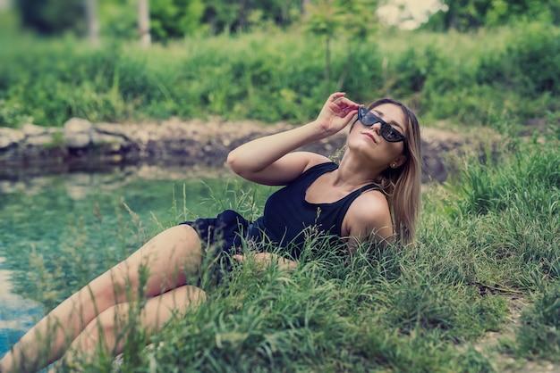 Aantrekkelijke vrouw genieten van natuur in de buurt van pond, zonnige dag