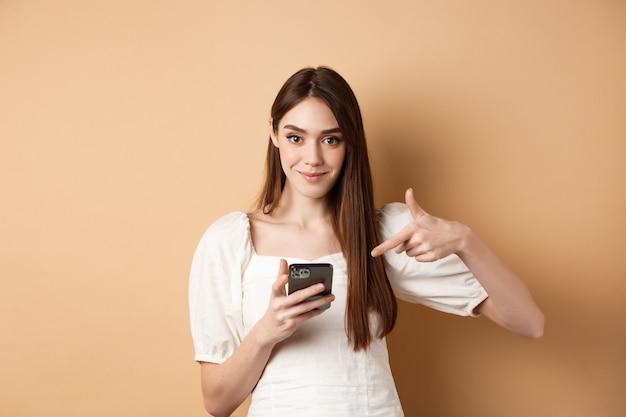 Aantrekkelijke vrouw glimlachend en wijzend op smartphone, online aanbod tonen op telefoon, staande op beige achtergrond.