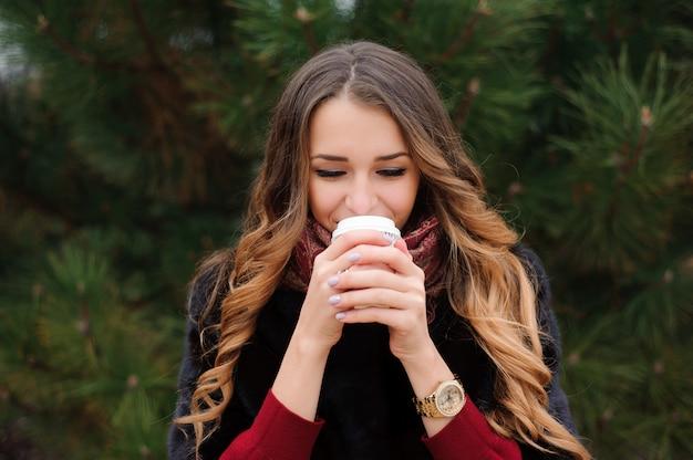 Aantrekkelijke vrouw heeft een koffiepauze op straat in herfstdag.