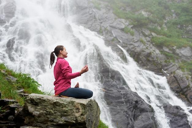 Aantrekkelijke vrouw het praktizeren yoga op rots dichtbij mooie balea-waterval in roemenië