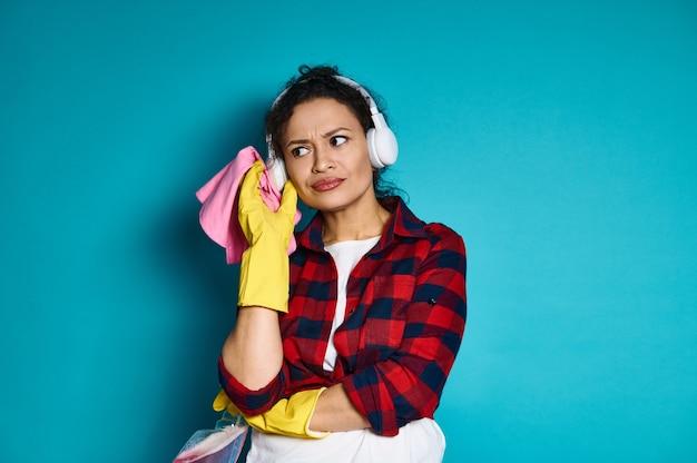 Aantrekkelijke vrouw, huisvrouw, staande tegen blauw met het schoonmaken van gereedschappen en benodigdheden, aandachtig kijkend, met een peinzende blik