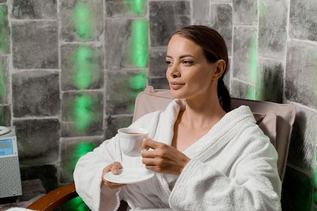 Aantrekkelijke vrouw in badjas met kopje thee ontspannen in de zoutkamer in de spa.