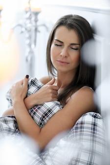 Aantrekkelijke vrouw in bed voor zichzelf met dekbed
