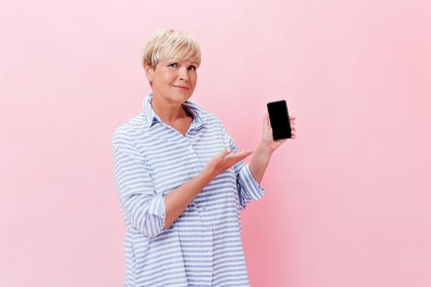 Aantrekkelijke vrouw in blauwe outfit toont zwarte telefoon op roze achtergrond