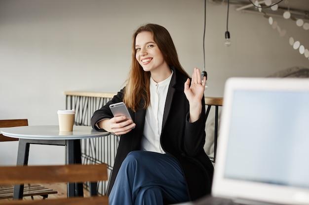 Aantrekkelijke vrouw in café met smartphone, hand zwaaien in groet, hallo zeggen
