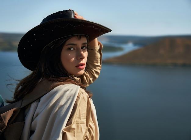 Aantrekkelijke vrouw in cowboyhoed die zich op hoge heuvel bevindt