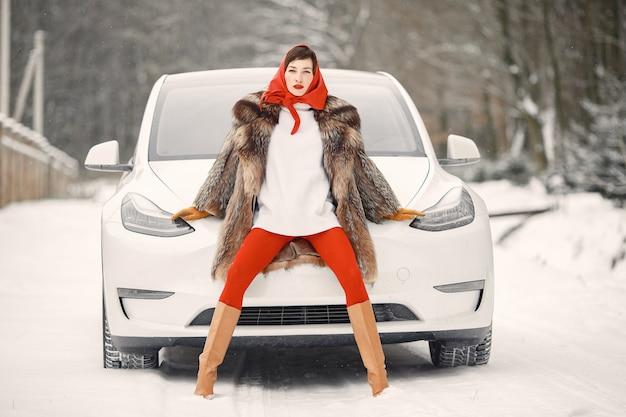 Aantrekkelijke vrouw in de winter buiten met witte auto