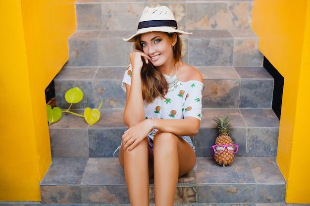 Aantrekkelijke vrouw in de zomer glimlachend dragen strohoed blootsvoets zitten in gedrukte t-shirt zomer mode vakantie