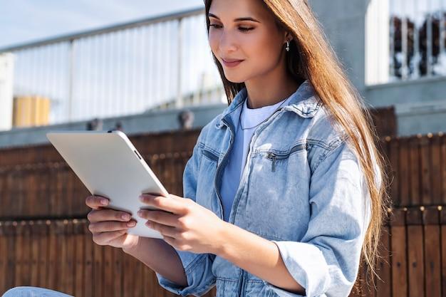 Aantrekkelijke vrouw in denim kleding zit op een bankje, houdt slimme tablet in haar handen. portret van mooie vrouw