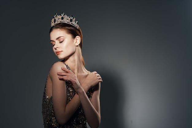 Aantrekkelijke vrouw in een gouden jurk met een kroon op haar hoofd decoratie studio. hoge kwaliteit foto
