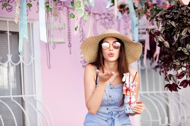 Aantrekkelijke vrouw in een hoed met brede rand blaast een kus. vrouw houdt milkshake in haar hand.
