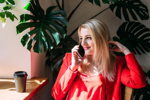 Aantrekkelijke vrouw in een rood jasje praat aan de telefoon